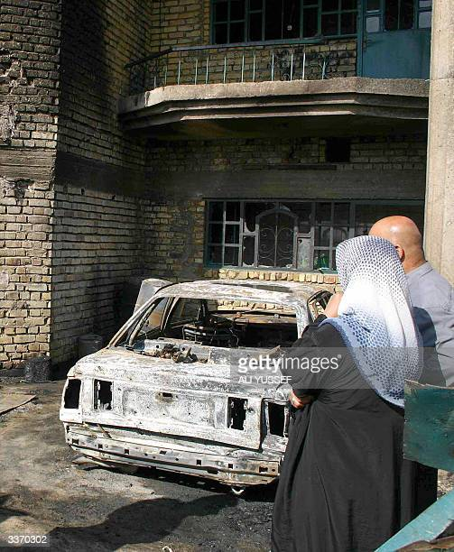 An Iraqi couple looks 15 April 2004 at the damage caused by US shelling on their house and car on the outskirts of Baquba 60 kms northeast of Baghdad...