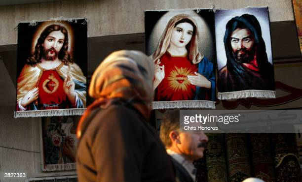 An Iraqi couple pass by rugs depicting Christian figures Jesus and Mary as well as the founder of Shia Islam Imam Ali December 22 2003 in Baghdad...