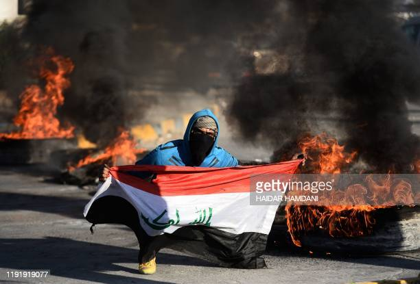 An Iraqi demonstrator carries a national flag while posing next to burning tyres as angry protesters blocked roads in the central shrine city of...