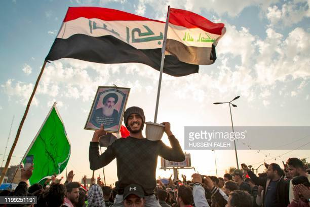 TOPSHOT An Iraqi demonstrator carries a portrait of Grand Ayatollah Ali Sistani during an antigovernment demonstration in the southern city of Basra...