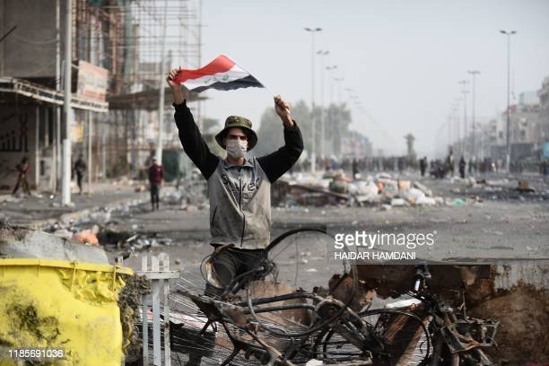 TOPSHOT An Iraqi demonstrator carries the national flag in the southern Iraqi Shiite holy city of Najaf on December 1 2019 Protesters have hit the...