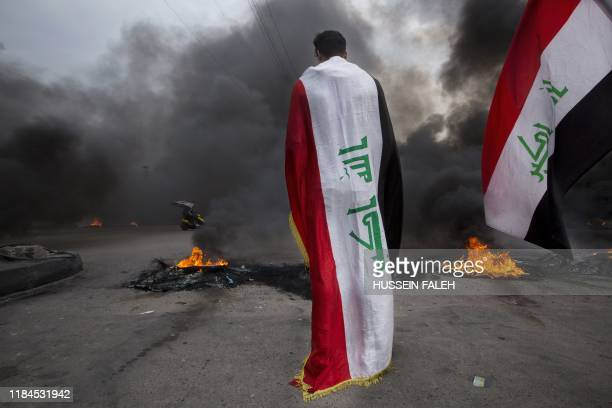 An Iraqi demonstrator clad with the national flag stands in front of burning tyres blocking a street amid a general strike in the southern city of...