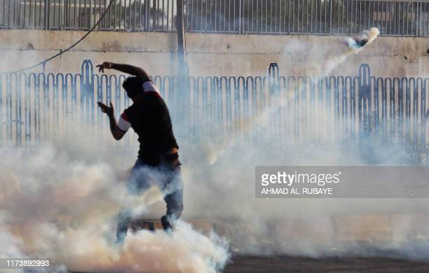 TOPSHOT An Iraqi demonstrator gestures amidst smoke from burning tyres and tear gas during a demonstration against state corruption failing public...