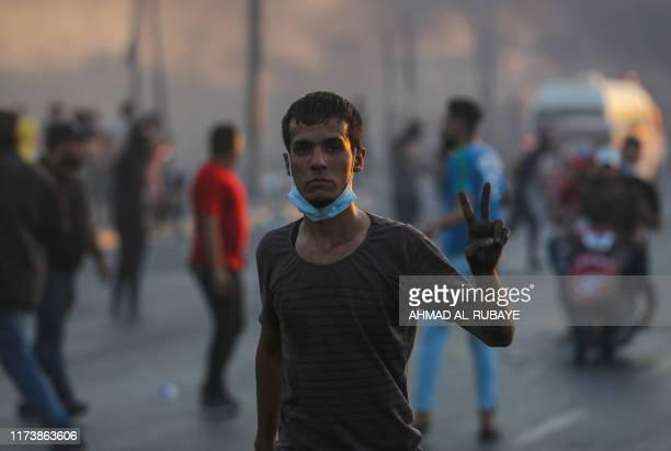 TOPSHOT An Iraqi demonstrator gestures with the vsign for victory during a demonstration against state corruption failing public services and...