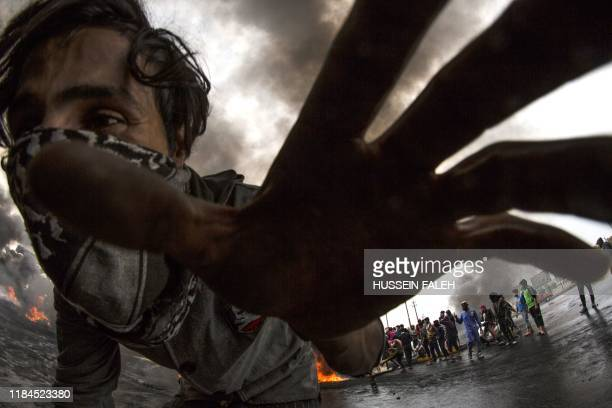 An Iraqi demonstrator runs as others burn tyres to cut-off roads in the southern city of Basra on November 25, 2019.