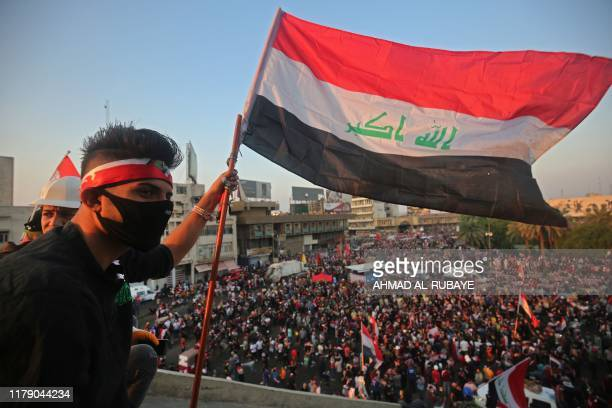 An Iraqi demonstrator waves his country's national flag from atop a vacant Turkish Restaurant overlooking the alJuhuriya bridge during ongoing...
