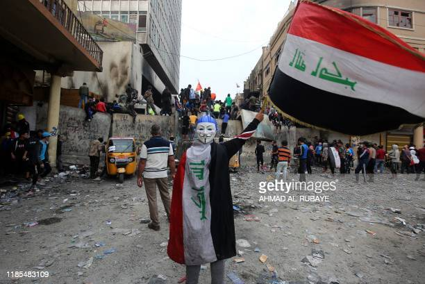 An Iraqi demonstrator wearing a Guy Fawkes mask in reverse and draped in a national flag waves another national flag before others celebrating the...
