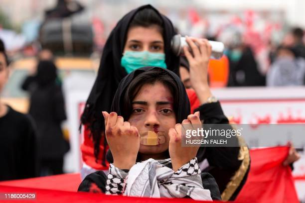 An Iraqi demonstrator with make-up to represent violence takes part in an anti-government march in the center of the southern city of Basra on...