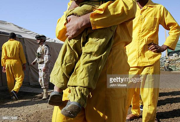 An Iraqi detainee embraces his son during family visitation hour at the Abu Ghraib Prison October 28 2005 on the outskirts of Baghdad Iraq Detainees...