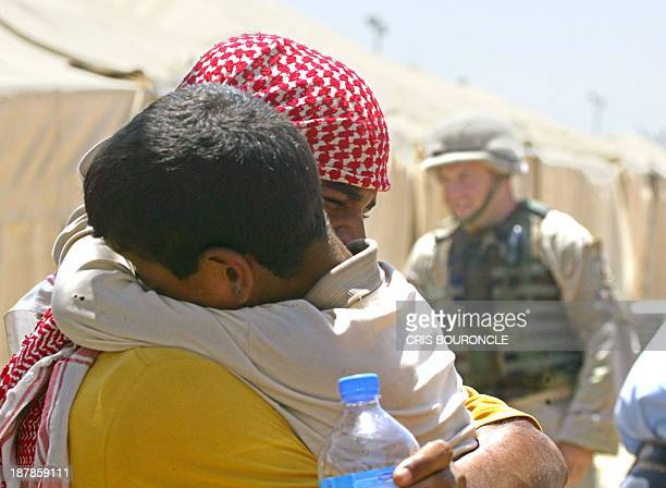 An Iraqi detainee embraces his young son at the end of an hour of visitation inside the dreaded prison of Abu Ghraib 30 Kms west of Baghdad 19 June...