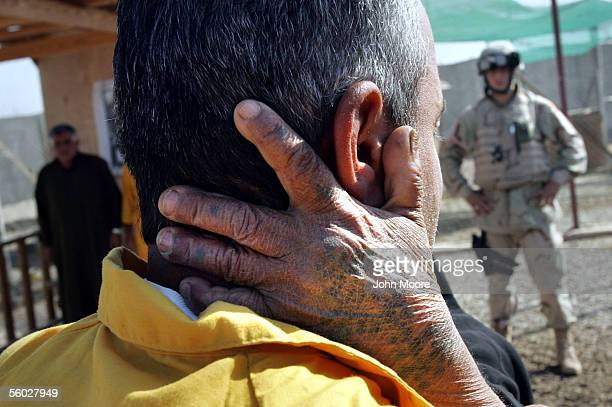 An Iraqi detainee is embraced by his mother as an American guard stands by at the Abu Ghraib Prison October 28 2005 on the outskirts of Baghdad Iraq...