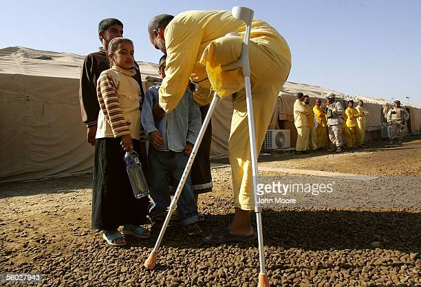 An Iraqi detainee is greeted his children during a family visitation hour at the Abu Ghraib Prison October 28 2005 on the outskirts of Baghdad Iraq...