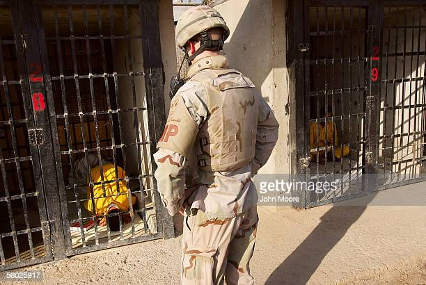 An Iraqi detainee prays alone as an American military policeman looks on during traditional Friday prayers in solitary confinement at the maximum...