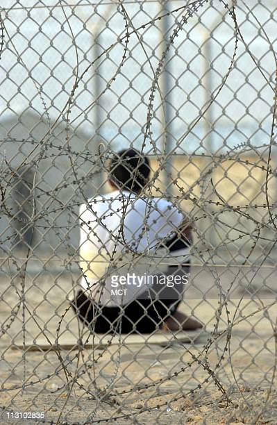 An Iraqi detainee sits alone behind the razorwire fences that close off highsecurity compounds at Camp Bucca the USrun detention center 300 miles...