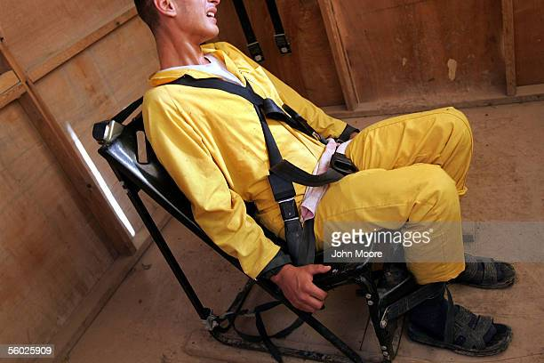 An Iraqi detainee weeps while tied down in a 'humane restraint chair' at the maximum security section of the Abu Ghraib Prison October 28 2005 on the...
