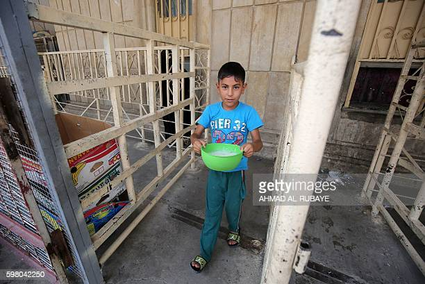 An Iraqi displaced child carries a bowl on August 31 2016 during a food distribution for displaced and impoverished families at the shrine of the...