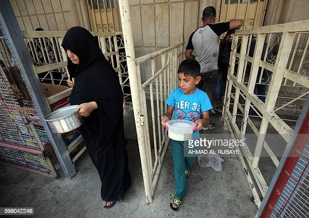 An Iraqi displaced child carries a plastic food container on August 31 2016 during a food distribution for displaced and impoverished families at the...
