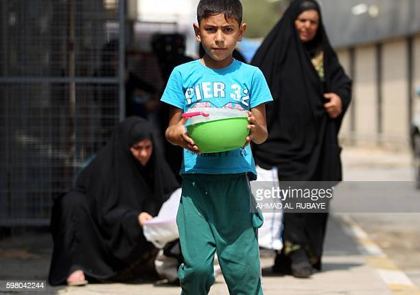 An Iraqi displaced child carries bowls on August 31 2016 during a food distribution for displaced and impoverished families at the shrine of the...