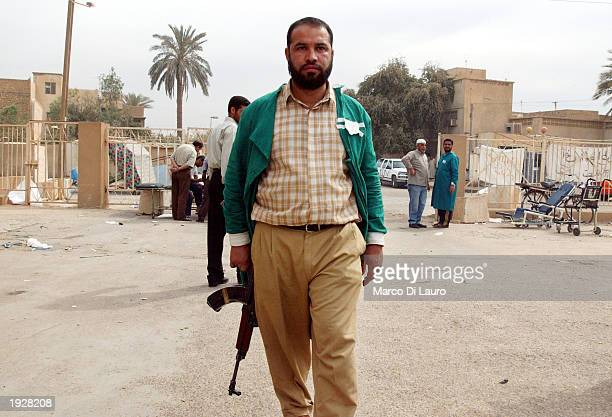 An Iraqi doctor holds a rifle to guard the North Baghdad's alKindi Hospital from looters April 13 2003 in Baghdad Iraq Widespread looting continues...