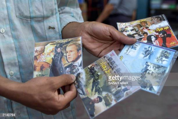 An Iraqi DVD seller displays his Saddam Hussein video CDs titled Saddam's Memoirs The Fall of Baghdad and Hala's Birthday Party at the 'Souk...