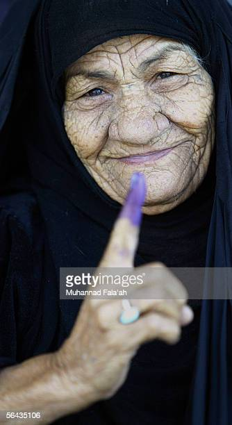 An Iraqi elderly woman shows her inked finger after voting at a polling station on December 15 2005 in Baghdad Iraq Iraqis went to the polls for the...
