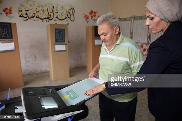 An Iraqi election registrar assists a voter in placing his ballot through an electronic counting machine into a ballot box at a poll station in the...