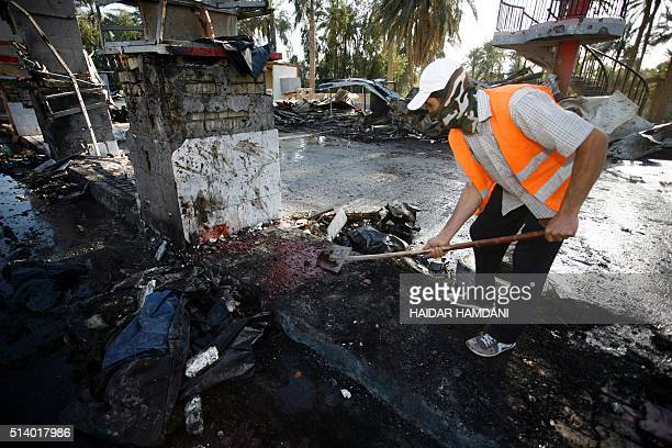 An Iraqi emergency responder clears debris from the site of a truck bomb that exploded at a crowded checkpoint in the Iraqi city of Hilla south of...