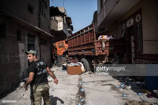 An Iraqi Emergency Response Division soldier looks back as he walks towards a truck that has been wedged between buildings to give cover against...
