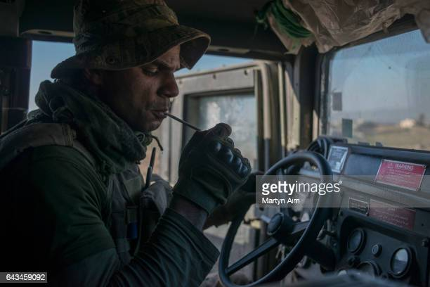 An Iraqi Emergency Response Division soldier soldier lights a cigarette in his Humvee before entering the Islamic State occupied village of Abu Saif...