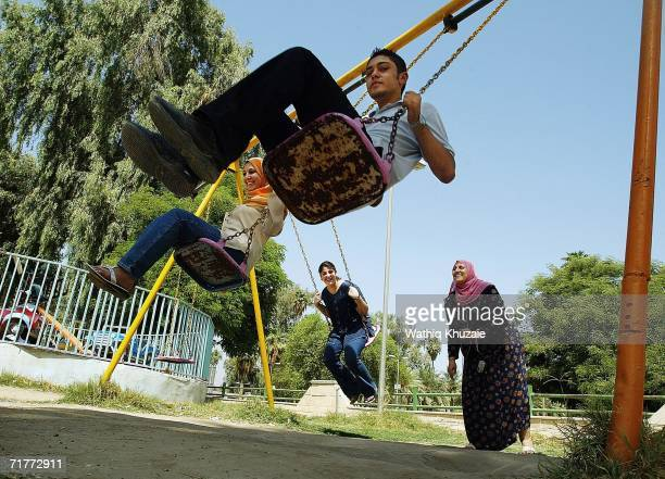 An Iraqi family enjoy the swings at Baghdad Zoo on September 2 2006 in Baghdad Iraq Sectarian violence is on the rise as previous days witnessed a...