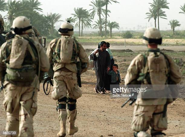 An Iraqi family flees past advancing US Army soldiers from the 1st Battalion 14th regiment of the 25th Infantry Division during a battle with...