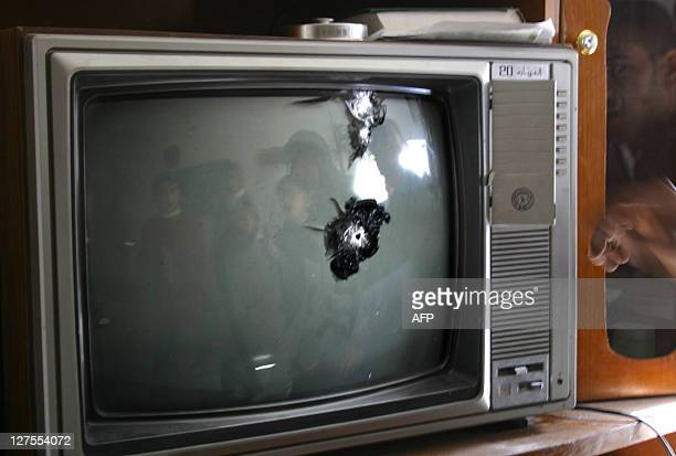 An Iraqi family is reflected on the screen of their television set which was hit by gunfire in Ramadi 100km west of Baghdad in a shootout in which an...