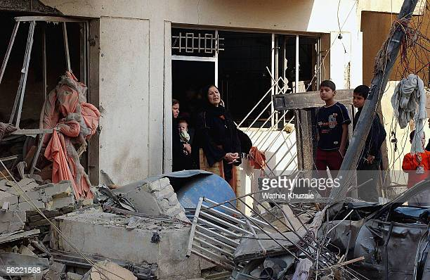 An Iraqi family look out from their apartment in the collapsed building where two suicide car bombs exploded near an Interior Ministry building...