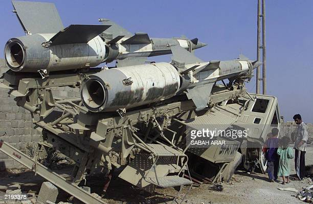 An Iraqi family passes surfacetoair rockets abandoned at scrap yard in Baghdad 16 July 2003 Much of toppled leader Saddam Hussein's armor has ended...