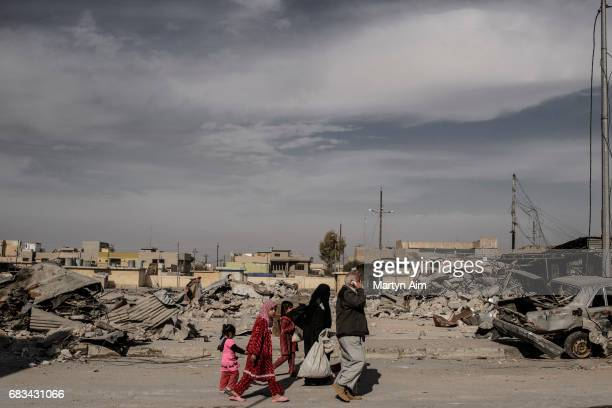 An Iraqi family returning home after displacment due to the war pass the ruins of the liberated district of Al Jazaer in eastern Mosul recently...