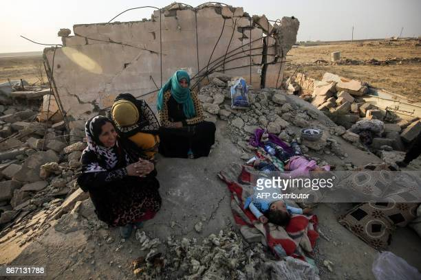 An Iraqi family sits on the rubble of their home in the village of Barzan, in the Zummar area of Nineveh province, northwest of Mosul, on October 27,...