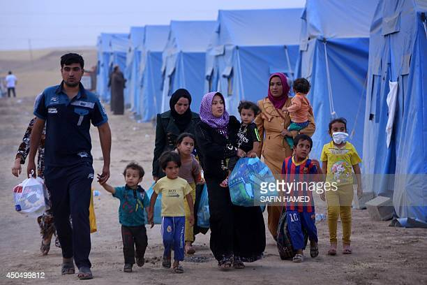 An Iraqi family walks past tents at a temporary camp set up to shelter Iraqis fleeing violence in Iraq's northern Nineveh province on June 12 in Aski...