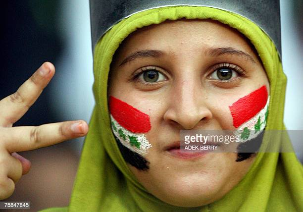 An Iraqi fan cheers for her team before the start of the final match of the Asian Football Cup 2007 between Iraq and Saudi Arabia at the Bung Karno...