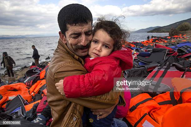 An Iraqi father cries as he holds his daughter after arriving safely on Greek shores October 25 on Lesbos Cold weather and rough seas have done...