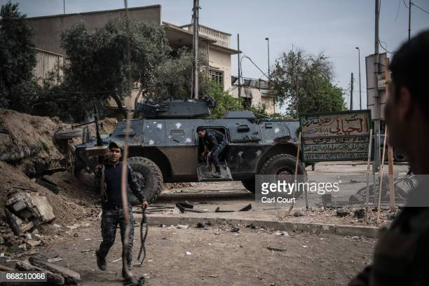 An Iraqi federal policeman disembarks from an armoured personnel vehicle during the battle to recapture west Mosul from Islamic State on April 12...