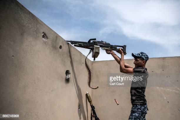 An Iraqi federal policeman fires a machine gun at a nearby Islamic State position during fighting in west Mosul on April 8, 2017 in Mosul, Iraq....