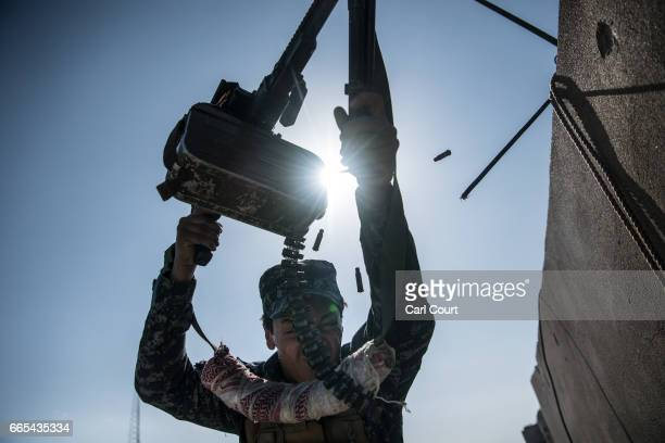An Iraqi federal policeman fires a machine gun at an Islamic State position on a nearby rooftop during fighting in west Mosul on April 6, 2017 in...
