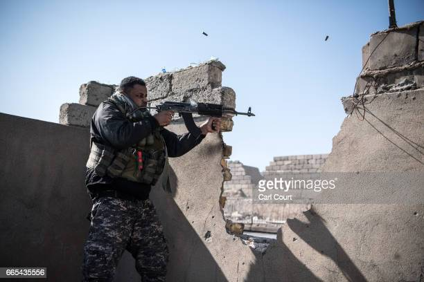 An Iraqi federal policeman fires at an Islamic State position on a nearby rooftop during fighting in west Mosul on April 6 2017 in Mosul Iraq Iraqi...
