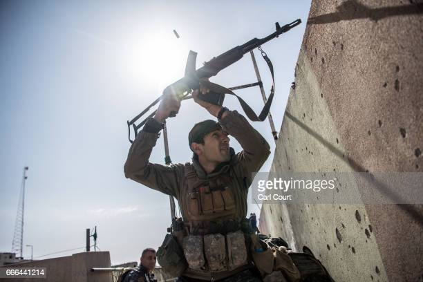 An Iraqi federal policeman fires at an Islamic State position on a nearby rooftop during fighting in west Mosul on April 6, 2017 in Mosul, Iraq....