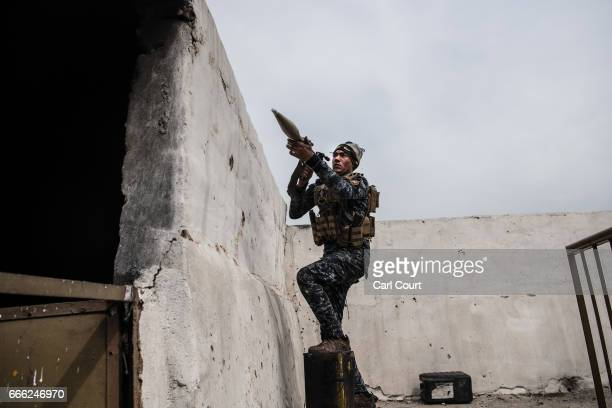 An Iraqi federal policeman prepares to fire a rocket propelled grenade at an Islamic State position on a nearby rooftop during fighting in west Mosul...