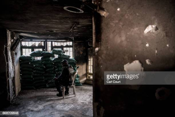 An Iraqi federal policeman sits on a chair behind sandbags as he mans a position overlooked by an Islamic State sniper during the battle to recapture...