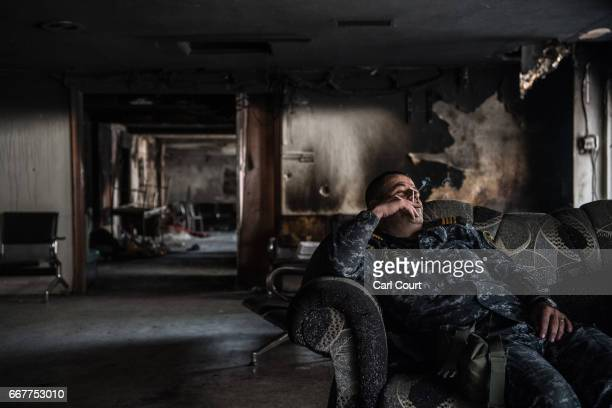 An Iraqi federal policeman smokes a cigarette as he relaxes between firefights during the battle to recapture west Mosul from Islamic State, on April...