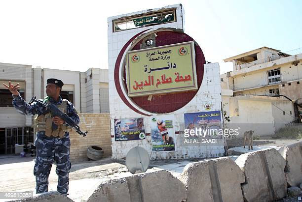 An Iraqi Federal policeman stands at a checkpoint in the centre of the city of Tikrit on April 15 as they guard the empty houses and shops that were...