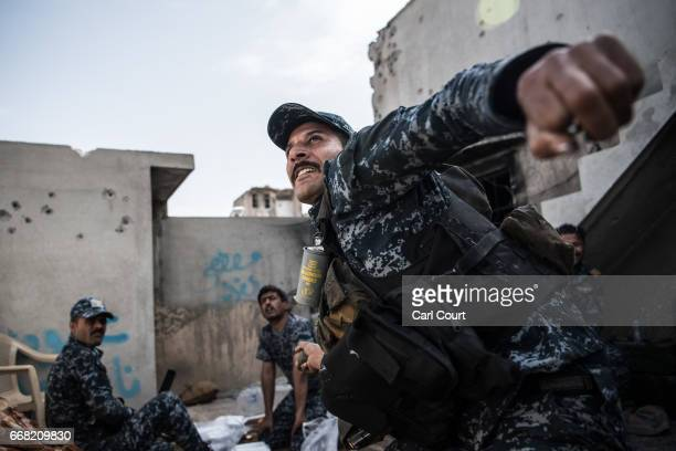 An Iraqi federal policeman throws a handgrenade at an Islamic State position on a nearby rooftop during the battle to recapture west Mosul on April...
