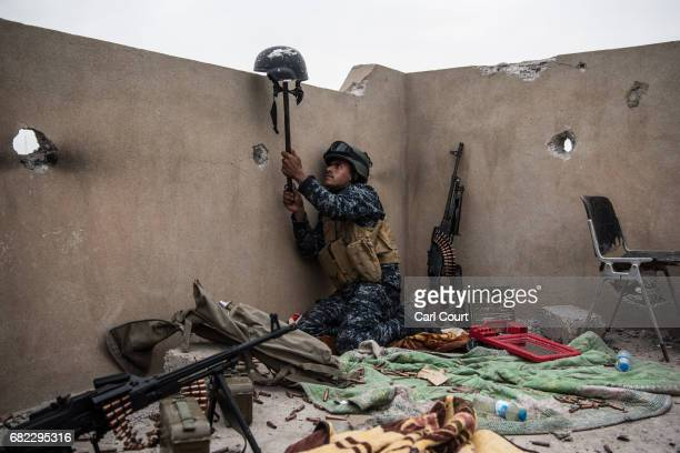 An Iraqi federal policeman uses a helmet on a stick to try and draw fire from an Islamic State sniper in an attempt to make him reveal his position...